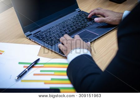 Businessmen Are Analyzing Stock Market Trading Of The Stock Market On His Desk