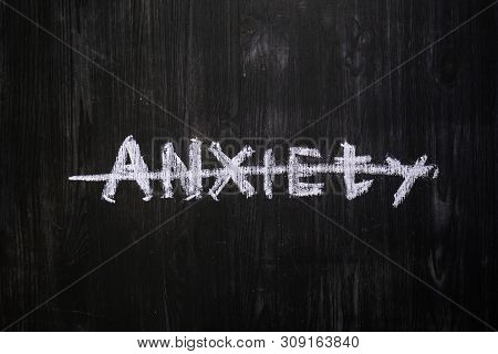 Anxiety Word Handwritten And Crossed Out On Black Wood Background. Sign, Concept Of Mental Issues So