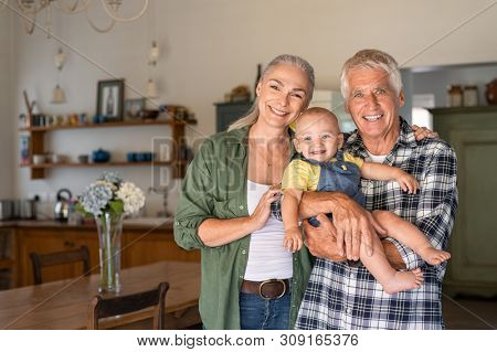 Happy senior man and mature woman playing with little baby while looking at camera. Portrait of grandmother and old grandfather standing with toddler and copy space. Grandparents and cute child.