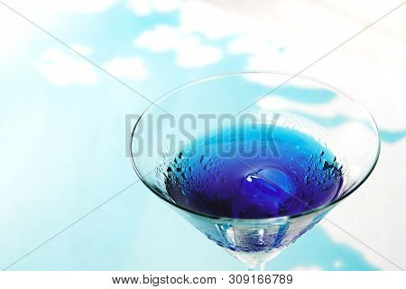 Fresh Purple Butterfly Pea Or Blue Pea Flower And Juice In Glass On Table Blue And White Background