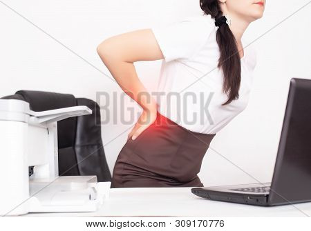 Girl Office Worker Holding Her Aching Back From A Chair, The Concept Of Back Pain In Office Workers,