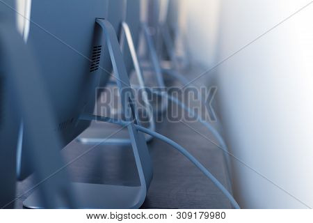 perspective closeup view with shallow depth of field of row of desktop workstation computers with cables in a digital college training centre poster