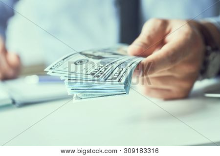 Businessman Giving Money Us Dollar Banknotes And Holding Cash In Hands. Money Credit Concept. Toned