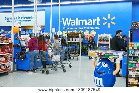 Montreal, Canada - April 30, 2019: People At Cashier In Walmart Store. Walmart Is An American Multin