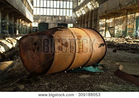 Radioactive Warning On Old Rusty Barrel In Destroyed And Forgotten Building. Radiation Symbol With R
