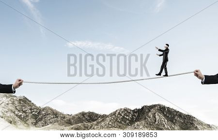 Businessman Walking Blindfolded On Rope Above High Mountains As Symbol Of Hidden Threats And Support