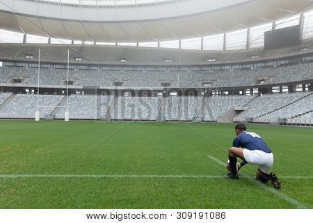 Rear view of male rugby player placing rugby ball on a stand in stadium
