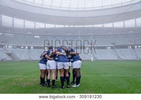 Side view of group of male rugby players forming huddles in the morning at stadium