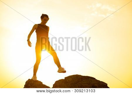 Young Beautiful Woman Walking on the Rocks in the Mountains at Hot Summer Sunset. Travel and Adventure Concept.