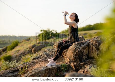 Young Woman Resting and Drinking Water after Trail Running Outdoor. Workout Exercise at Hot Beautiful Summer Sunset. Sport and Healthy Active Lifestyle Concept.