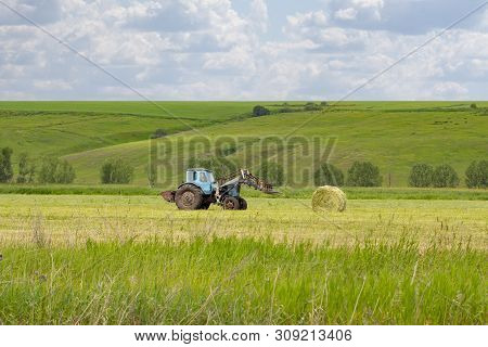Rural Life, A Rural Tractor Collects A Sheaf Of Hay On A Green Meadow. Round Hay Roll, Pet Food, Hay