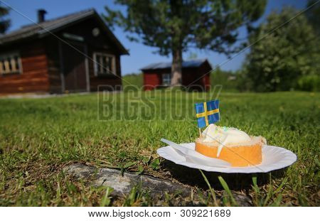 Cake In The Grass On The National Day Of Sweden.