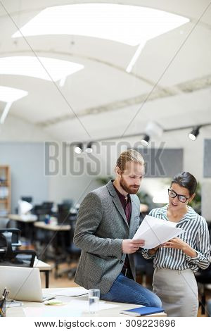 Portrait Of Successful Businessman Discussing Document While Talking O Female Secretary In Office, C
