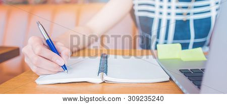 Woman Hand Working At A Computer And Writing On A Notepad With A Pen In The Office.