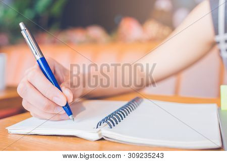 Woman Hand Writing On A Notepad With A Pen In The Office.