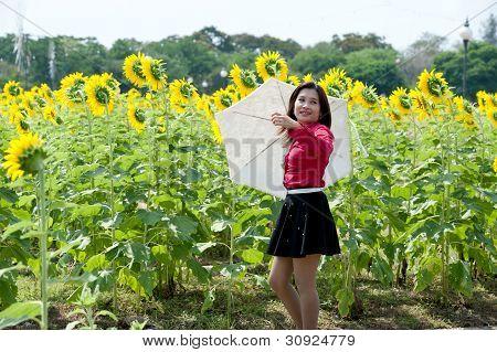 Pretty Asian Woman In Red Dress Hold Umbrella Is Joyfully  In Sunflower Field .