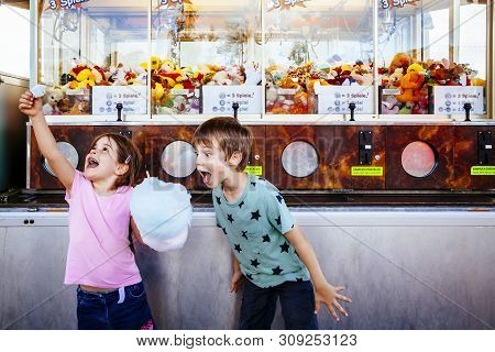 Photo Of A Brother And Sister Eating A Big Cotton Candy At An Amusement Park.