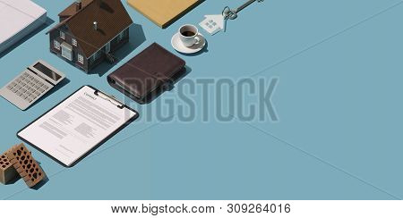 Real estate agent desktop with model house, contract and bricks: home ownership, investment and loans concept poster