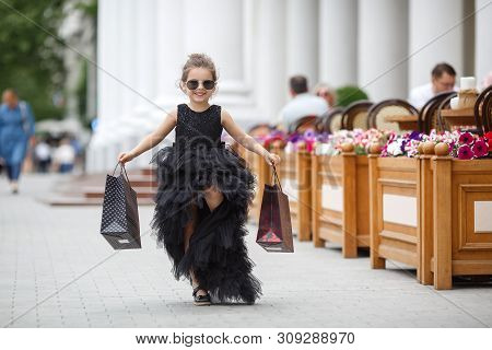 Cute Little Caucasian Girl Child Having Shopping Fun.fashion Trend. Fashion Shop. Little Girl With B