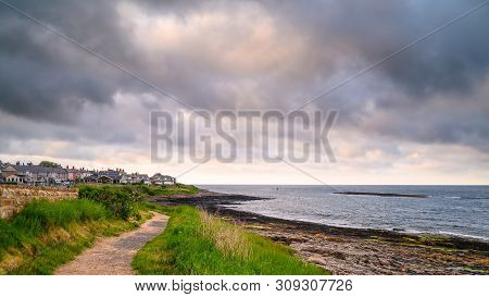 Northumberland Coast Path At Craster, With The Rocky Shoreline At Craster Village On The Northumberl