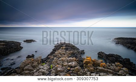 Long Exposure At Craster Rocks, With The Rocky Shoreline At Craster Village On The Northumberland Co