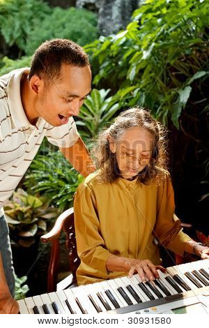 Ethnic Old Mother And Son Sing and Play Piano