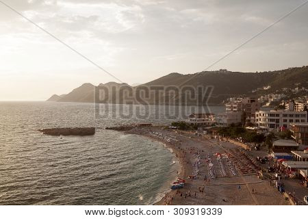 Top View Of The Illuminated By The Setting Rays Of The Sun The Beach On The Adriatic Sea In The Town