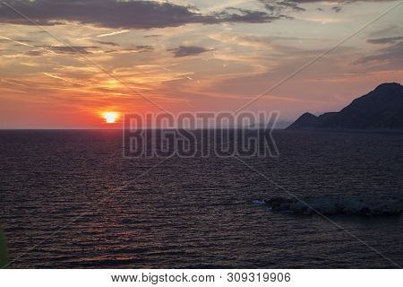 Beautiful View Of The Sun Hiding Behind The Sea Surface In Dobra Voda, Montenegro.  The Sunset Sky I