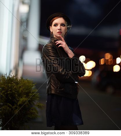 brooding young woman looking at the lights in the night city. poster