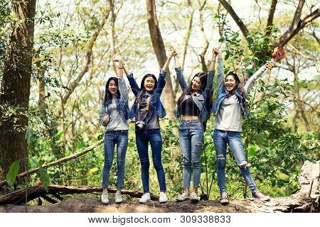 Group Of Women Walking Through Woodland.group Of Women Smiling Walking With Backpack.travel And Hike