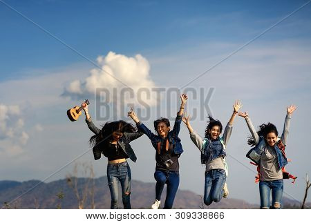 A Group Of Women Jump Together In The Grass Field.beautiful Group Of Girls Traveling Together On Hol