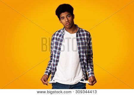Poverty And Absence Of Money. Unemployed Sad Afro Guy Showing Empty Pockets, Yellow Background
