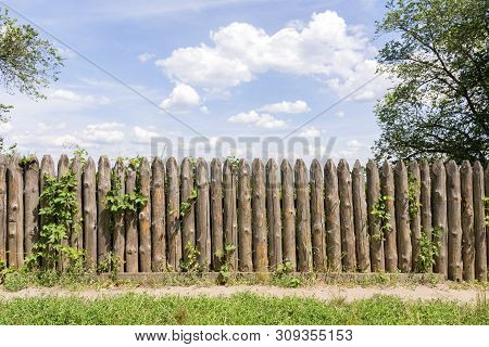 Old Fence Of Logs. Palisade Against The Blue Sky