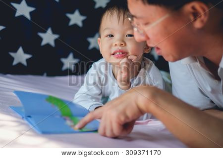 Father And Cute Little Asian 2 - 3 Years Old Toddler Boy Child Reading Bedtime Story Book, Lying In