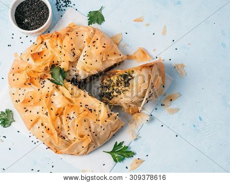 Greek Pie Spanakopita On White Baking Paper Over Blue Background. Ideas And Recipes For Vegetarian O