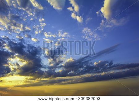 Blue yellow sunny sky and clouds background of dramatic cloudscape and skyscape with clouds in sunset poster