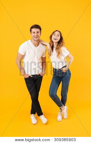 Full length portrait of beautiful couple man and woman in basic t-shirts standing together and laughing at camera isolated over yellow background