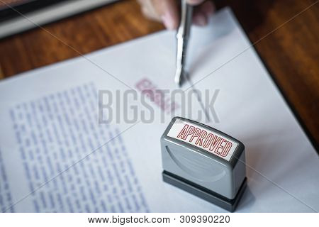Close Up Hands Of Businessman Signing And Stamp On Paper Document To Approve Business Investment Con