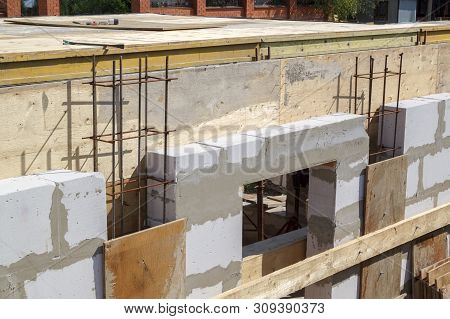 view of the wooden formwork with metal holders, which will be filled with the overlap between the floors in the country house under construction from the foam block poster
