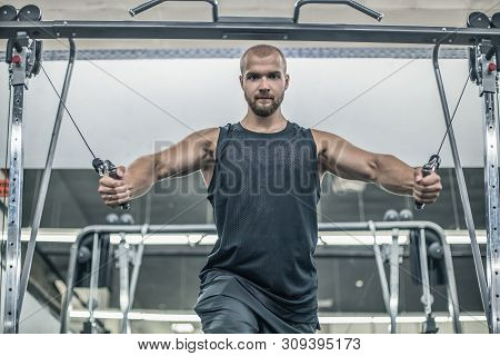 Brutal Handsome Caucasian Bodybuilder Working Out In The Gym Training Chest Pumping Up Pectoral Musc