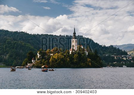 Bled, Slovenia - September, 8 2018: Beautiful Close Up View On The Bled Island And Pletna Boats With