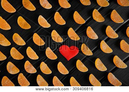 Heart And Fruit Marmalade In The Form Of Mandarin Lobules Lie On Dark Painted Boards. The Combinatio