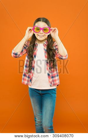 Looking Trendy. Fashionable Party Girl On Orange Background. Adorable Party Girl Wearing Fancy Glass