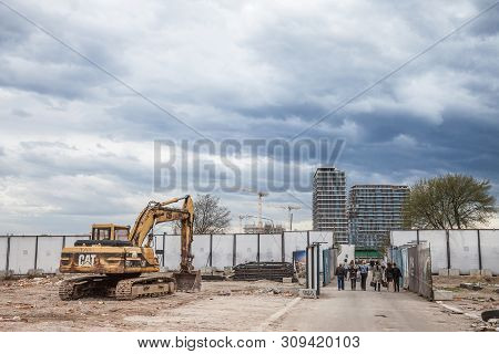 Belgrade, Serbia - March 31, 2018: People Passing By A Cat Excavator In The Construction Site Of Beo