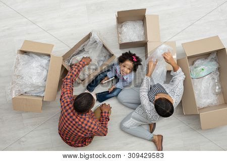 High angle view of happy African american family unpacking cardboard boxes in living room at home