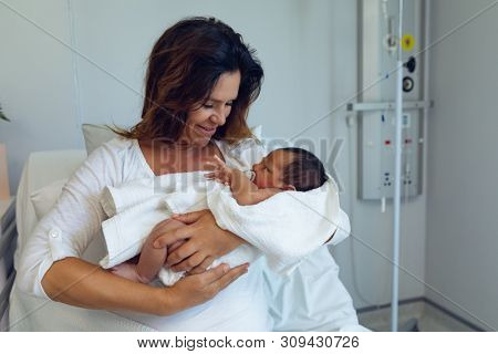 Front view of Caucasian mother holding her newborn baby child after labor in the ward at hospital