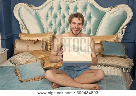 Already Found His Birthday Gift In Bed. Happy Man Holding Present Wrapped In Box. Sexy Man Smiling W
