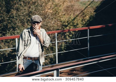 Bluesman With Guitar Case Smokes Cigarette On Railroad. Blues Musician With Cigarette On Railway. Co