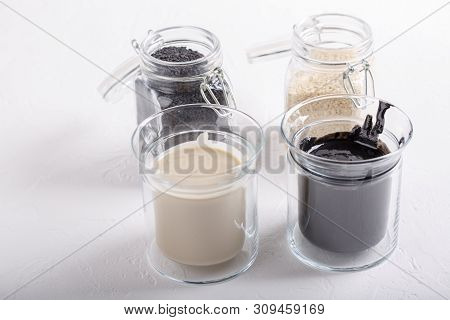 Black Tahini And White Tahini Sauce In Glass Jars On White Background. Natural Paste Made From Sesam