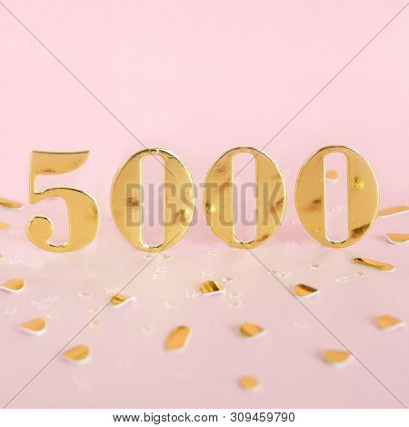 The Number 5000 In Golden Numbers On A Pink Background And Golden Confetti. Space For Text.